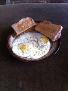2 eggs, 2 pieces of toast with butter and coffee with cream and sugar (not shown) - 343 calories.