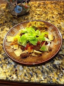 Organic tortilla chips, refried beans, ground beef, lettuce, cheese, ketchup (shh) and guacamole. Delicious! 542 calories!