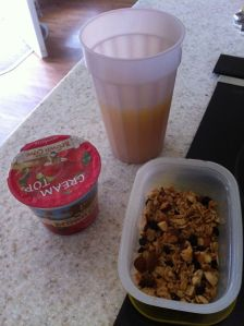Organic strawberry yogurt with homemade granola.  A cup of orange juice too!